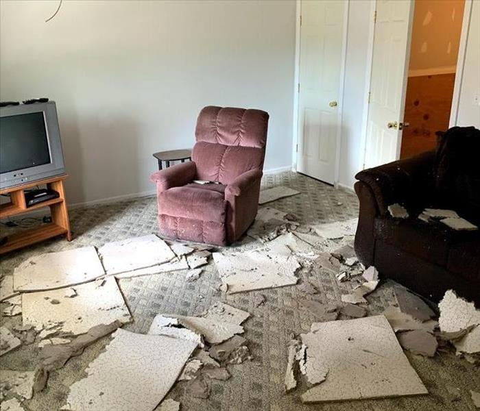 A basement with wet carpet covered in wet, soggy ceiling tiles and a recliner, couch, and tv stand.