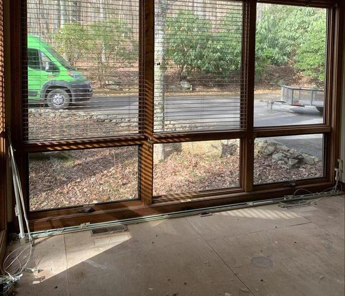 Carpet has been removed, only the subfloor remains. Big windows with the SERVPRO van outside.