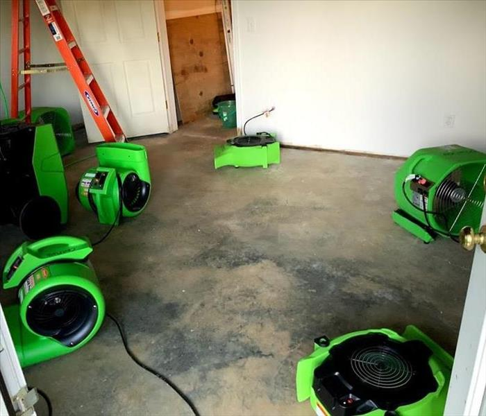 Concrete basement floor is dry with 4 green SERVPRO air movers placed in it.