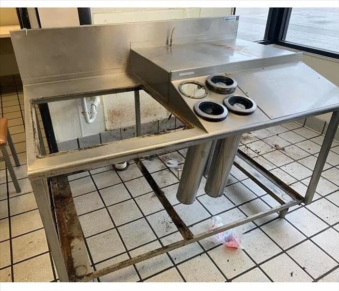A metal table and tile floor are very dirty. Covered with black grease and dirt.