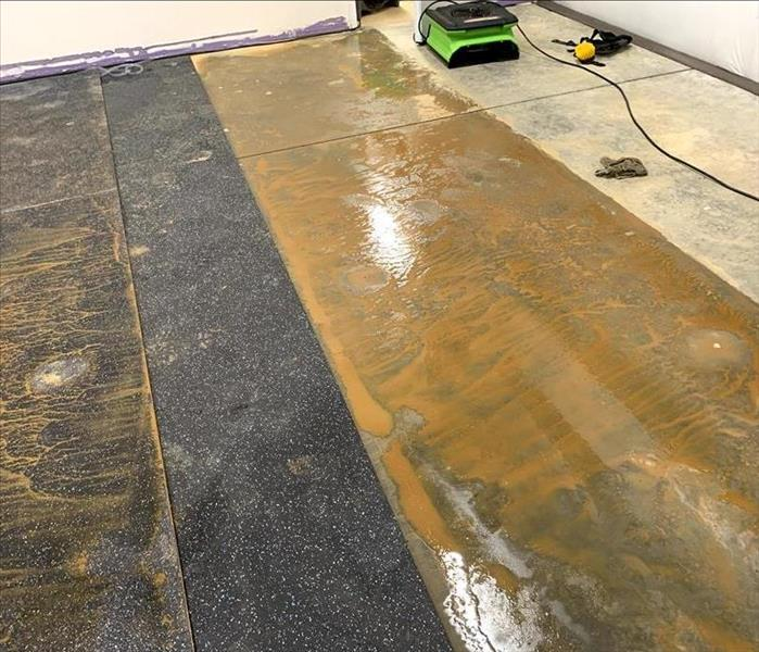 A concrete floor is wet and muddy. Dirty rubber mats have also been damaged on top of the concrete.